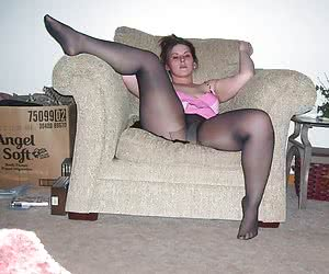 Chubby housewife in a black pantyhose spreads her legs in the chair