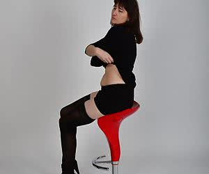 Posing on a swivel stool.With stockings mini skirt and blouse.A small strip and only the stockings nylons I keep on.