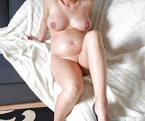 Veronica, pregnant blonde in blue lingerie and with high heels is sitting on a couch and stripping nude.