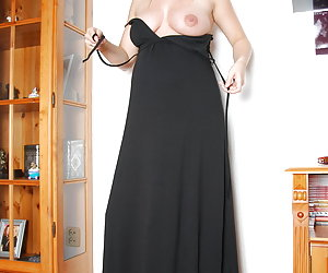 Veronica, pregnant blonde in long black dress is stripping nude, keeping only her high heel shoes on.