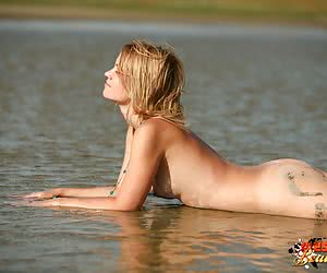Hot looking blonde posing nude and messy in the mud