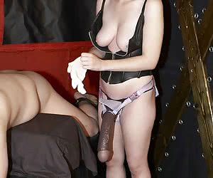 Beautiful Mistress Sarah penetrates male slave with a huge dildo. Another slave waits on his knees and watches.