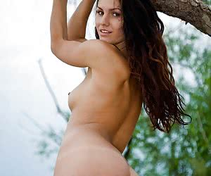 Hot vacation shots of a sexy brunette undressing and posing nude outside