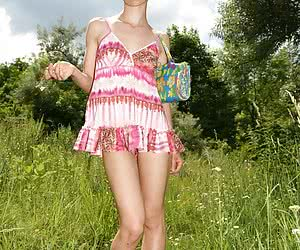 Skinny young beauty taking her pink clothes off and playing in the nude on the grass